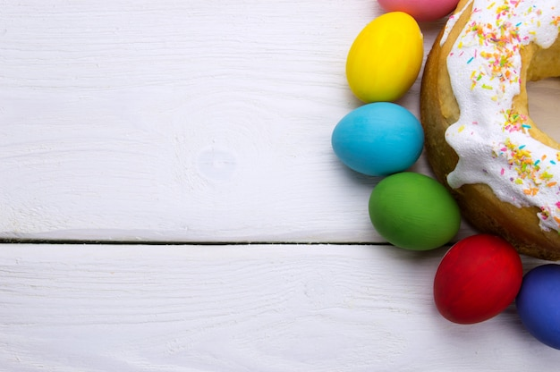 Easter eggs and easter cake on white wooden surface