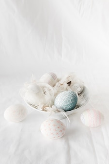 Easter eggs between feathers in bowl