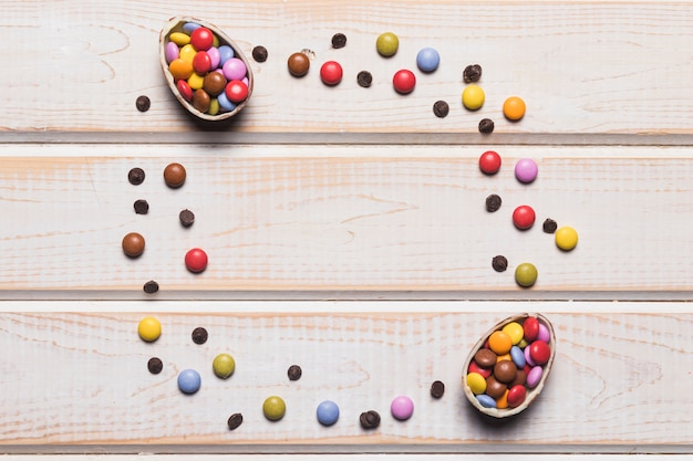 Easter eggs filled with colorful candies on wooden desk with space in the center for writing the text