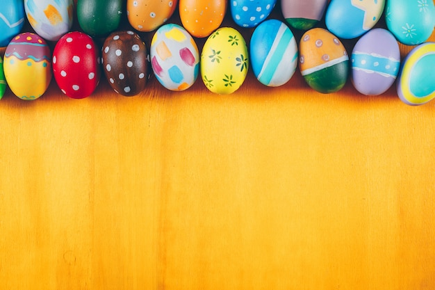 Easter eggs flat lay on yellow wooden background