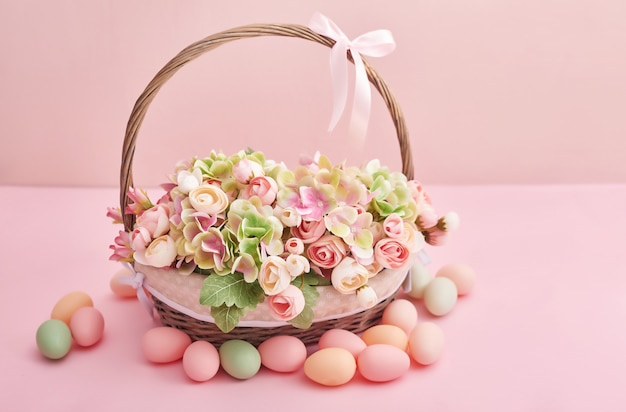 Easter eggs and flowers. easter basket with flowers and eggs on pink background