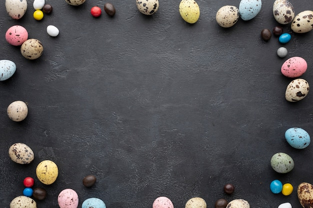 Easter eggs frame with candy on slate background