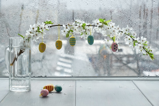 Easter eggs hanging from twig with white blossoms by the window on a rainy day