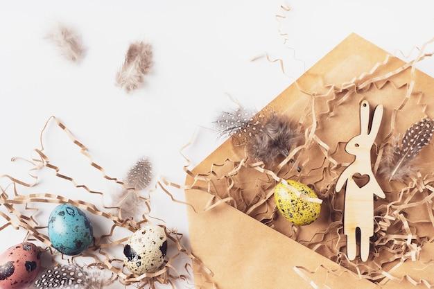 白い背景の上のクラフト封筒のイースターエッグ、ウサギ、羽、干し草。ホリデーメッセージハッピーイースター、対応コンセプト。フラットレイ、上面図。イースターカード。