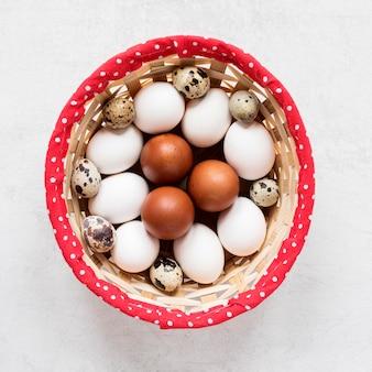 Easter eggs in hay basket flat lay