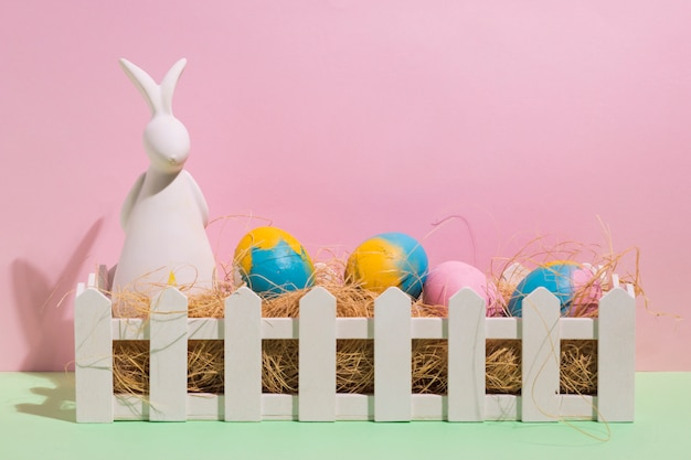 Easter eggs on hay in box with rabbit figurine