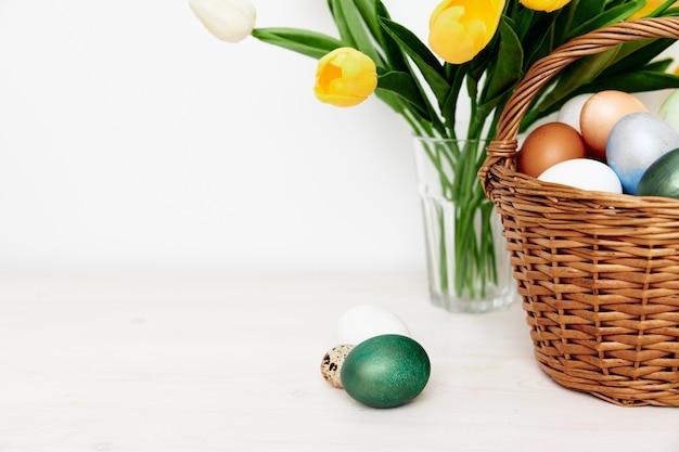 Пасхальные яйца в корзине и букет желтых цветов на столе