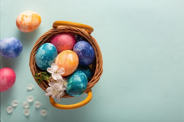 Пасхальные яйца в корзине на синем фоне