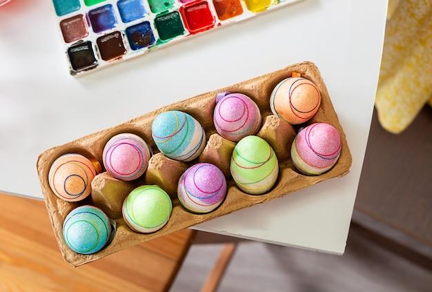 Пасхальные яйца в картонной коробке расписанные к празднику пасхи на столе рядом с красками