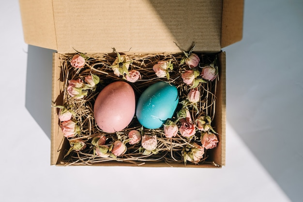 Пасхальные яйца в картонной коробке с цветами на белом фоне, вид сверху