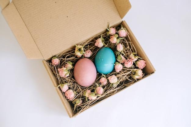 Пасхальные яйца в картонной коробке с цветами на белом фоне с копией пространства счастливой пасхи