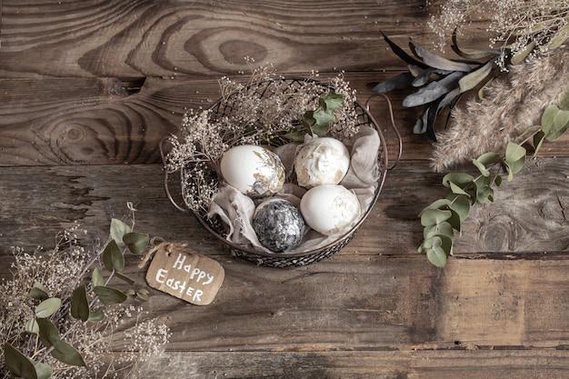 木製のテーブルの上にドライフラワーと装飾的なバスケットのイースターエッグ。ハッピーイースターのコンセプト。
