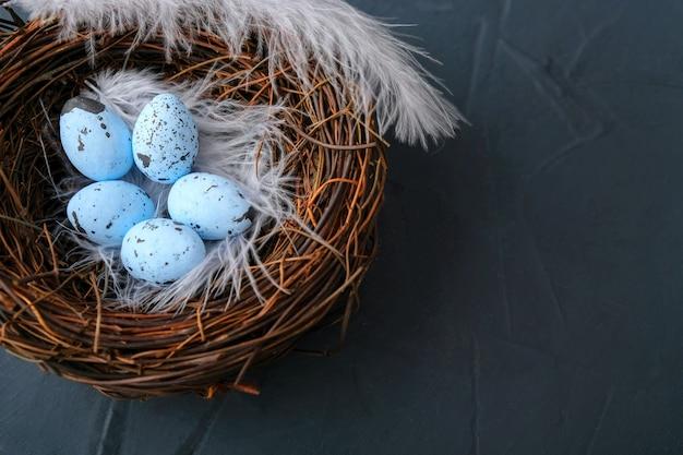青いテーブルの巣の中のイースターエッグ