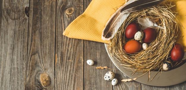 木製のテーブルの金属板に巣のイースターエッグ。ハッピーイースターのコンセプト