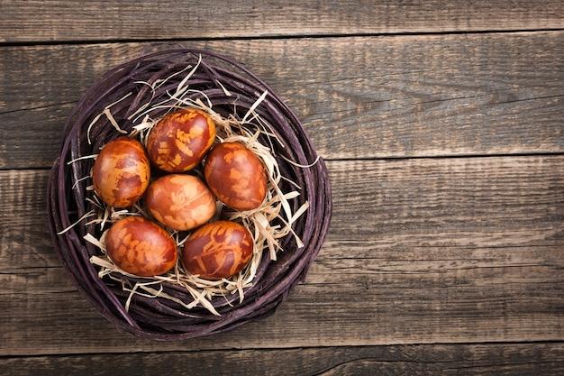 나무 배경에 둥지에 있는 부활절 달걀