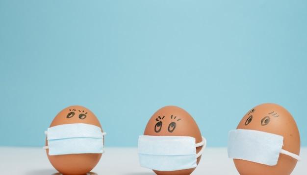 파란색 배경에 보호 의학 마스크에 부활절 달걀
