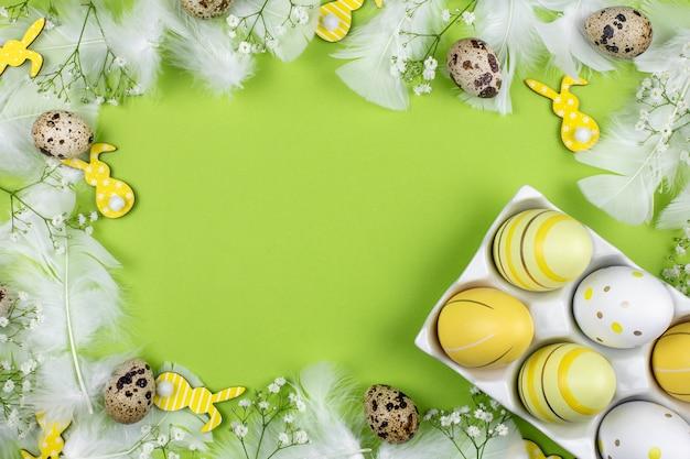 Пасхальные яйца в белом керамическом держателе, пасхальный кролик, перепелиные яйца, цветы и белые перья на зеленом фоне.