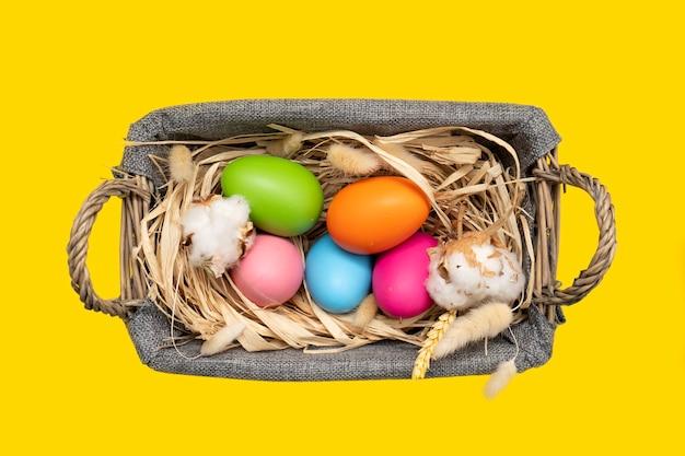 노란색 표면에 바구니에 부활절 달걀