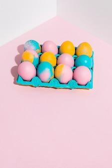 Пасхальные яйца в синей стойке на розовом столе