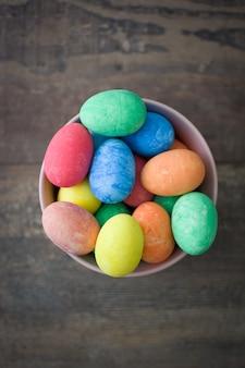 Пасхальные яйца в миску фон на деревянный стол сверху