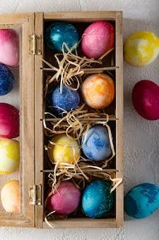 Пасхальные яйца в коробке с соломой.