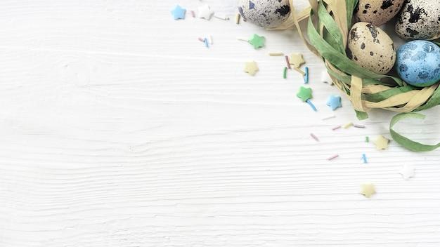흰색 나무 바탕에 장식 둥지에 부활절 달걀. 파스텔 색상 부활절 달걀