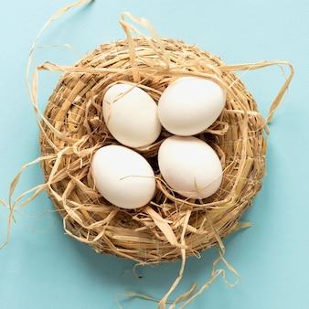 Пасхальные яйца в корзине сена вид сверху