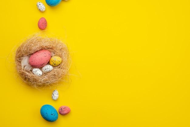 黄色の背景の上の巣のイースターエッグ。コピースペースで表示
