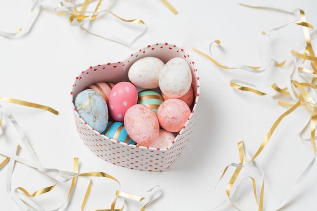 심장 모양의 상자에 파스텔 색상의 부활절 달걀. 행복한 부활절