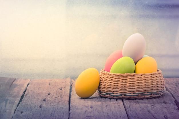 Пасхальные яйца в гнезде на деревенской деревянной доске