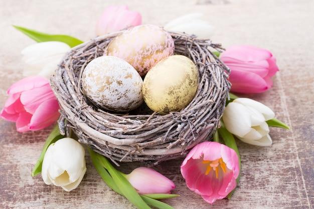 둥지와 튤립에있는 부활절 달걀