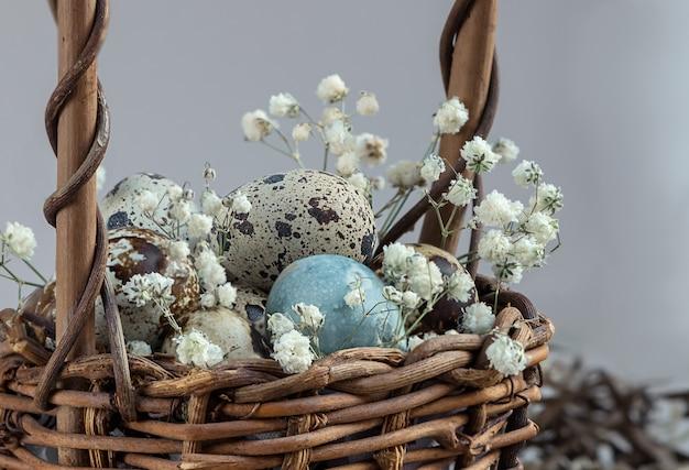 白い花で飾られた籐のバスケットのイースターエッグ。ハッピーイースターホリデーグリーティングカード