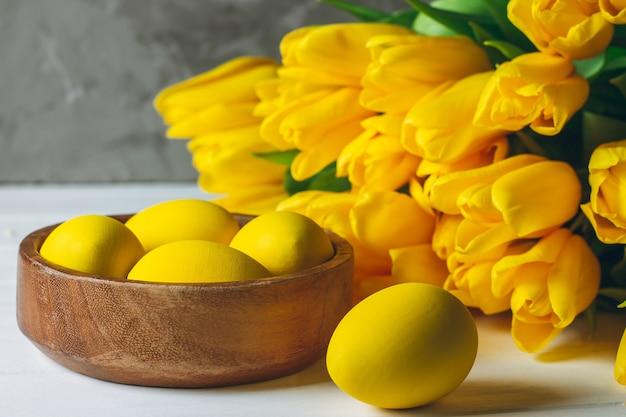 Пасхальные яйца в деревянной миске и букет ярко-желтых тюльпанов на белой деревянной поверхности на серой поверхности