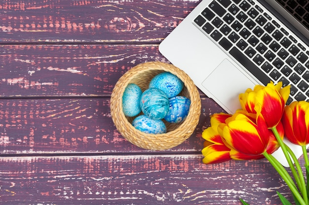 Easter eggs, laptop and bouquet of tulips.
