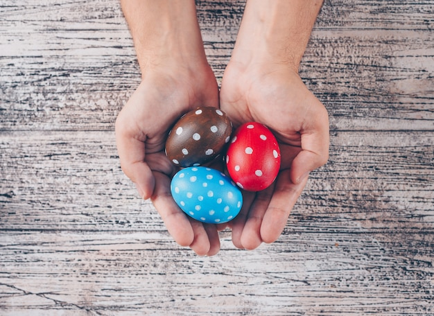 Easter eggs in man_s hands on wooden background.