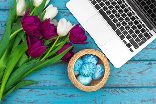 Easter eggs, mockup laptop and bouquet of tulips.