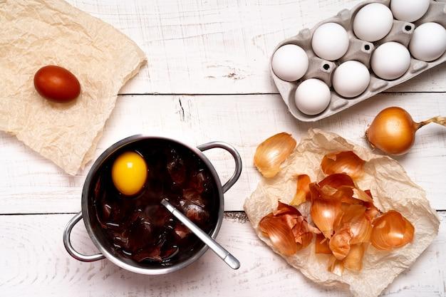 イースターエッグ、天然染料の着色プロセス、白い木製の背景に小さな鍋のタマネギの殻。