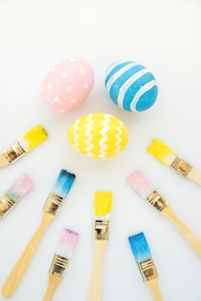 Easter eggs near brushes in paints