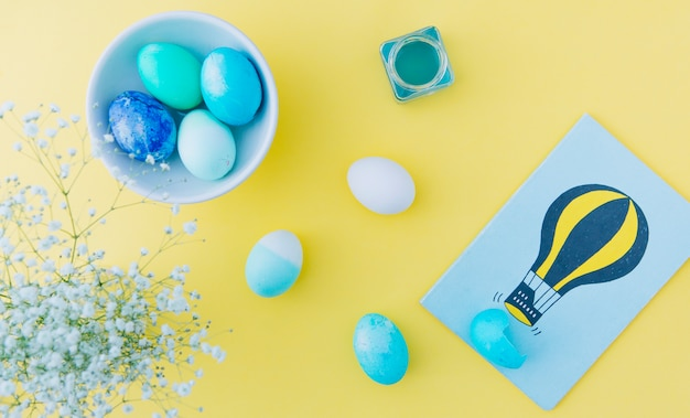 Easter eggs near can with dye liquid, bowl and picture near flowers