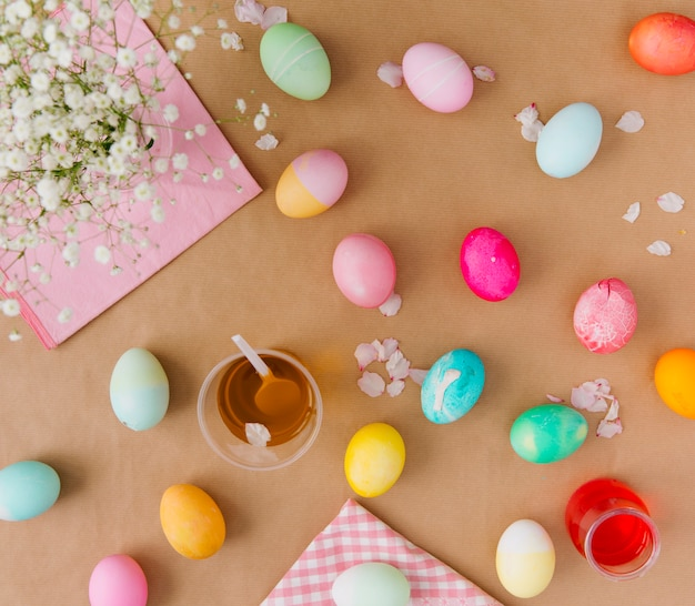 Easter eggs near cups with dye liquid, napkins and flowers