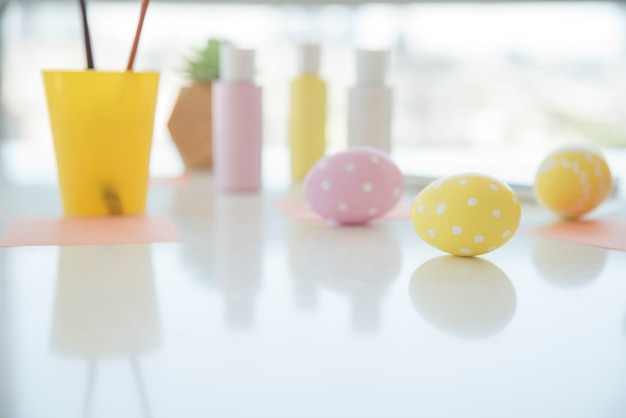 Easter eggs near sheets and colors on table