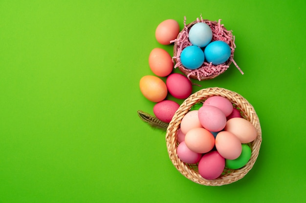 Easter eggs in a nest on green background close up
