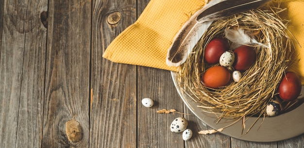 Easter eggs in a nest on a metal plate on a wooden table. happy easter concept