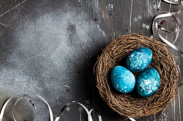Easter eggs in nest painted by hand in blue