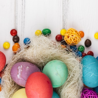 Easter eggs in nest with candies on table