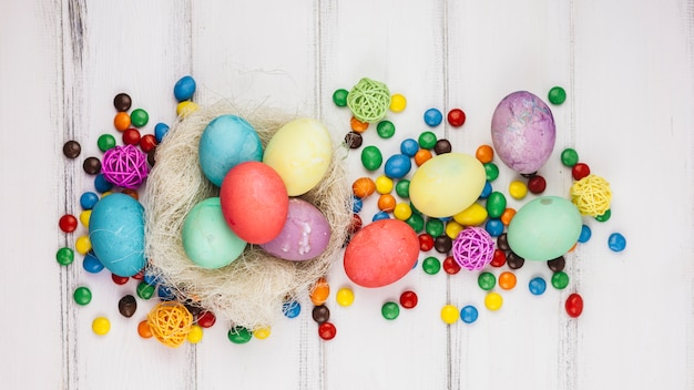 Easter eggs in nest with candies on wooden table