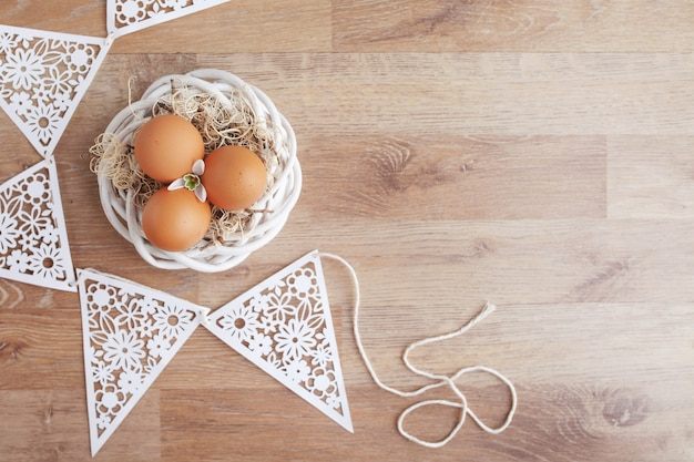 Easter eggs  in nest on wooden rustic table, holiday background for your decoration. spring and easter holiday concept with copy space.
