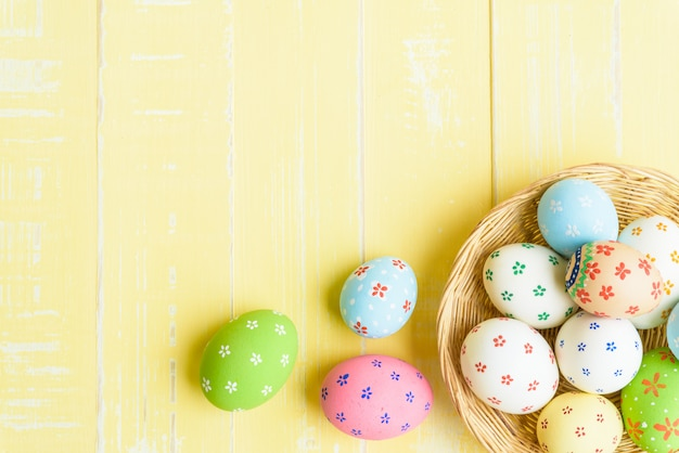 Easter eggs in nest on yellow wooden background.