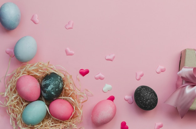 Easter eggs and nestle with eggs on pink