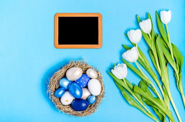 Пасхальные яйца синих цветов в гнезде из соломы, меловой доски и букет белых тюльпанов на синем фоне, копия пространства, плоская планировка